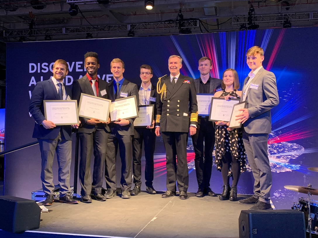 """The two first-place teams from the """"Swarm and Search AI Challenge: 2019 Fire Hack"""" were recognized during a special ceremony on board the HMS Queen Elizabeth Nov. 20, by Admiral Tony Radakin, First Sea Lord and Chief of the Royal Navy. From left, the team from the University of Michigan, including Matthew Romano, Prince Kuevor, and Jeremy Castagno. The team from the United Kingdom included Thomas Koeck, Connor McMullen, Lucy Bell, and Samuel Barkes. (Courtesy photo)"""