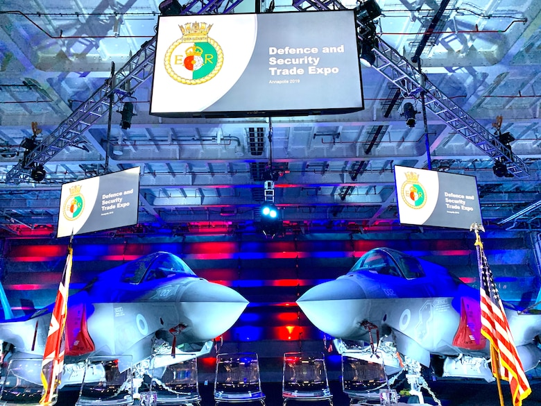 Two F-35 Joint Strike Fighter fast jets provided a powerful backdrop on the stage inside the aircraft hangar on board the HMS Queen Elizabeth Nov. 20 when the two winning teams from the Swarm and Search AI Challenge: 2019 Fire Hack, were recognized. (Courtesy photo)