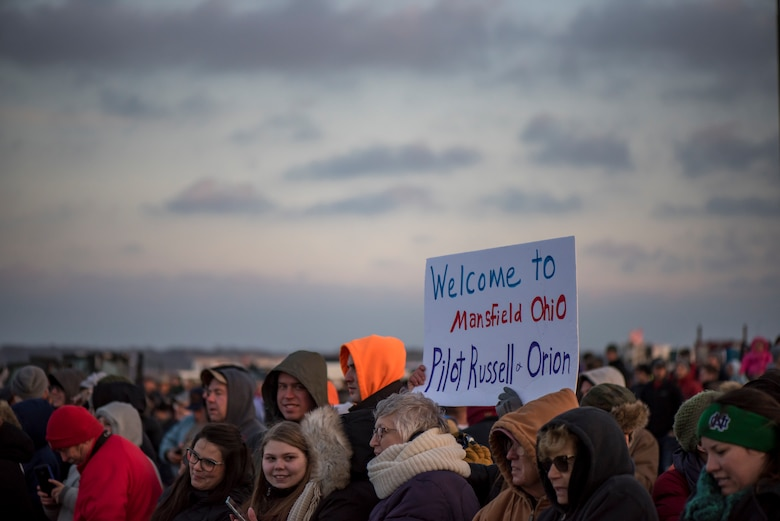 A photo of all the people who came to see the NASA Super Guppy at Mansfield Lahm Airport, holding up a sign that says Welcome to Mansfield Pilot Russell and Orion.