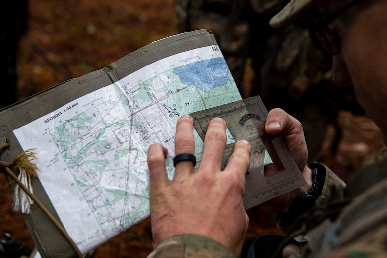 Airman 1st Class Dennis Hannas, an Air Force Ranger Assessment Course student, uses a protractor to pinpoint his location Nov. 15, 2019, at Moody Air Force Base, Ga. The course teaches students critical tasks such as land navigation, troop movements and shooting and maintaining weapons. Over the course of 19 days, the Ranger Assessment Course evaluates students to determine if they possess the knowledge, willpower and skill to attend Army Ranger School. (U.S. Air Force photo by Airman Azaria E. Foster)