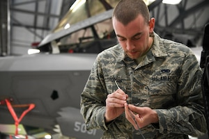 An Airman preps material for work on an F-35A canopy.