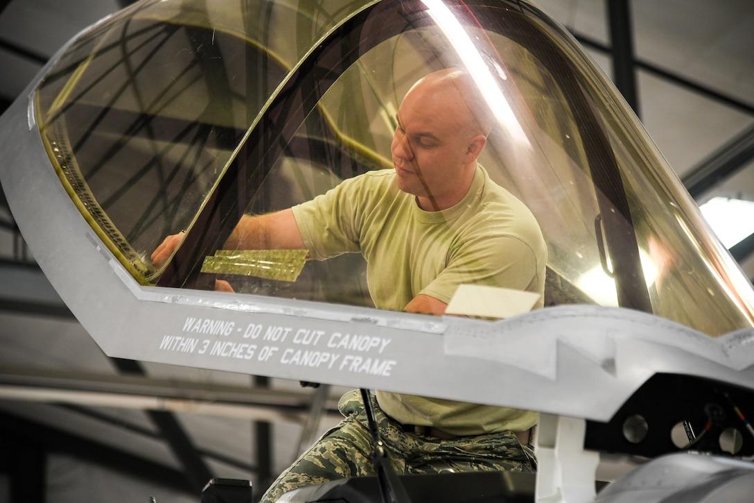 An Airman works on an F-35A canopy.