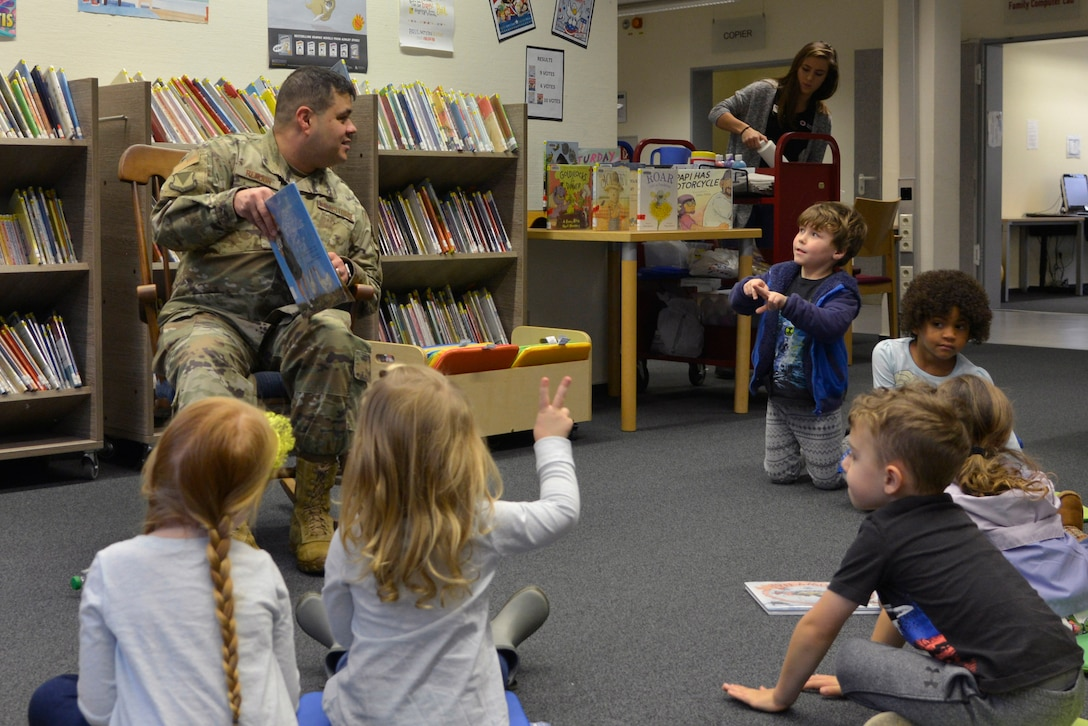 "U.S. Air Force Chief Master Sgt. Ernesto J. Rendon, 86th Airlift Wing command chief, answers questions from children during Story Time at Ramstein Library, Ramstein Air Base, Nov. 21, 2019. The story of the week, ""Mercedes and the Chocolate Pilot: A True Story of the Berlin Airlift and the Candy that Dropped from the Sky,"" helped give children an understanding of Air Force history in Germany. Afterward, children painted wooden airplanes as a takeaway reminder of the event. (U.S. Air Force photo by Airman 1st Class John R. Wright)"