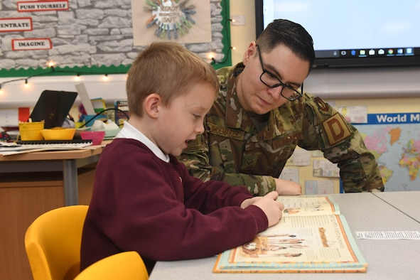 Senior Airman Andrew Shoemaker, 100th Logistics Readiness Squadron inspection apprentice, listens as a student reads a book at Houldsworth Primary School in Newmarket, England, Nov. 26, 2019. The purpose of the event was to build relations with the community while also focusing on the importance of reading for the children. (U.S. Air Force photo by Senior Airman Luke Milano)