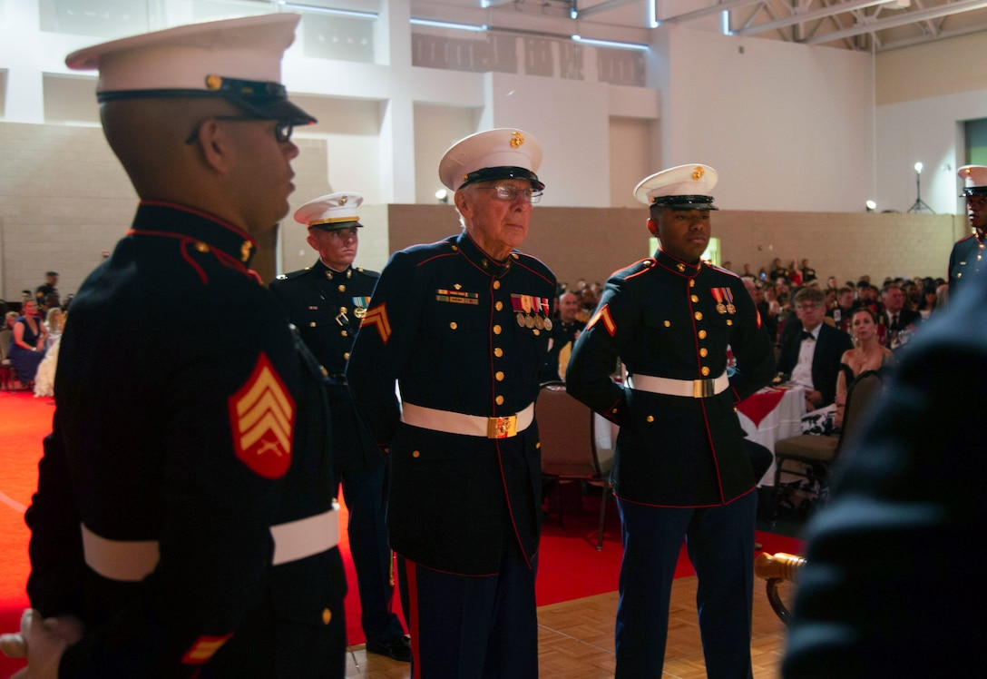 Appearing in authentic 1945-1948 Marine Corps dress blues with original regalia, 96-year-old World War II veteran and Marine Raider Cpl. Leonard B. Turner, oldest Marine present, stands next to 19-year-old Pfc. Ivan K. Lopez, the youngest Marine present, during the Marine Forces Special Operations Command's 244th Marine Corps Birthday Ball in Wilmington, N.C., Nov. 2, 2019.  Every year, each Marine Corps unit comes together and hosts a Marine Corps Birthday cake cutting to celebrate one more year since the birth of their Corps.  This celebration is an event that brings together Marines, old and young - enlisted and retired, and allows them to celebrate their commitment and dedication to the Marine Corps and strengthen their camaraderie and organizational esprit de corps.  This connection between the past and present can be seen throughout many traditions during the Marine Corps ball and is the foundation of this event each year.  One such tradition is the passing of birthday cake from the oldest Marine to the youngest Marine, which represents the passing of experience and knowledge from older generations to the newest generation of Marines.  The birthday cake is traditionally cut with the Mameluke sword, to honor Lieutenant Presley O'Bannon's assault of Derna, Tripoli in 1805, as a reminder that Marines are a band of warriors, committed to carrying the sword, so that the nation may live in peace.