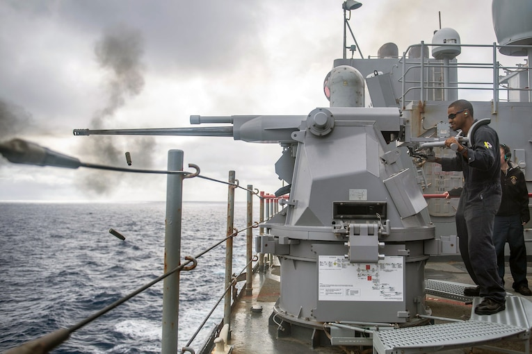A sailor stands on a ship and fire a large machine gun.