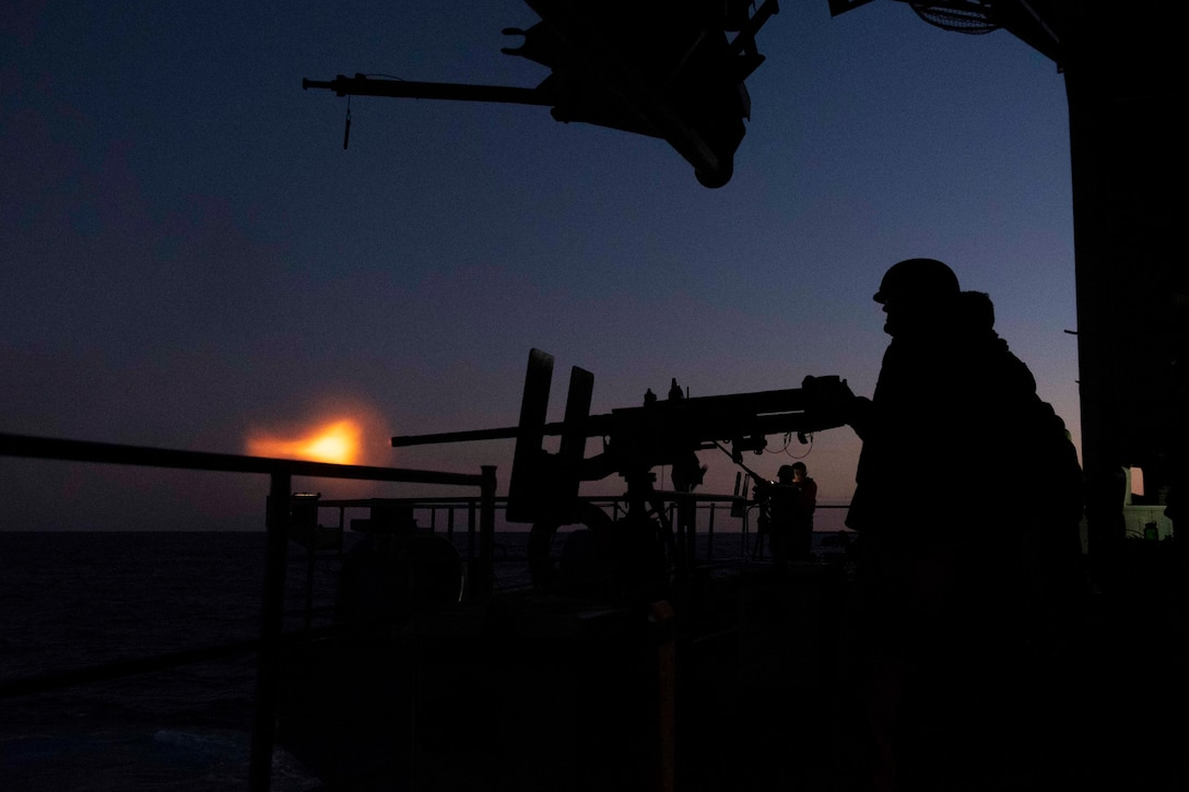 Sailors fire a machine gun from a military ship at twilight.