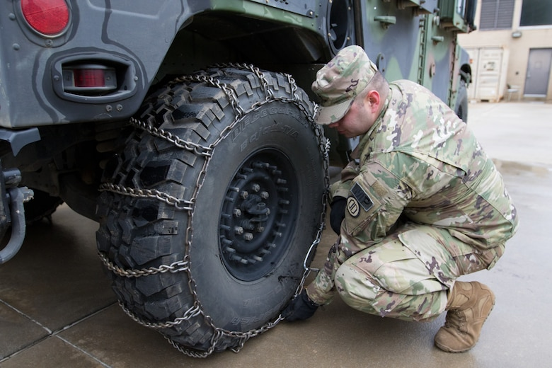 Sgt. Dannie Green, 128th Military Police Company, Alabama National Guard, installs snow chains on Humvees in preparation for winter storm response in Fort Payne, Alabama, Jan.6, 2017. (Photo by Army Sgt. William Frye.)