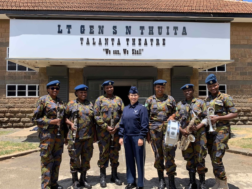 A female U.S. Air Force member poses with six Kenyan Air Force Band members, all of whom are holding instruments, outside a theater.