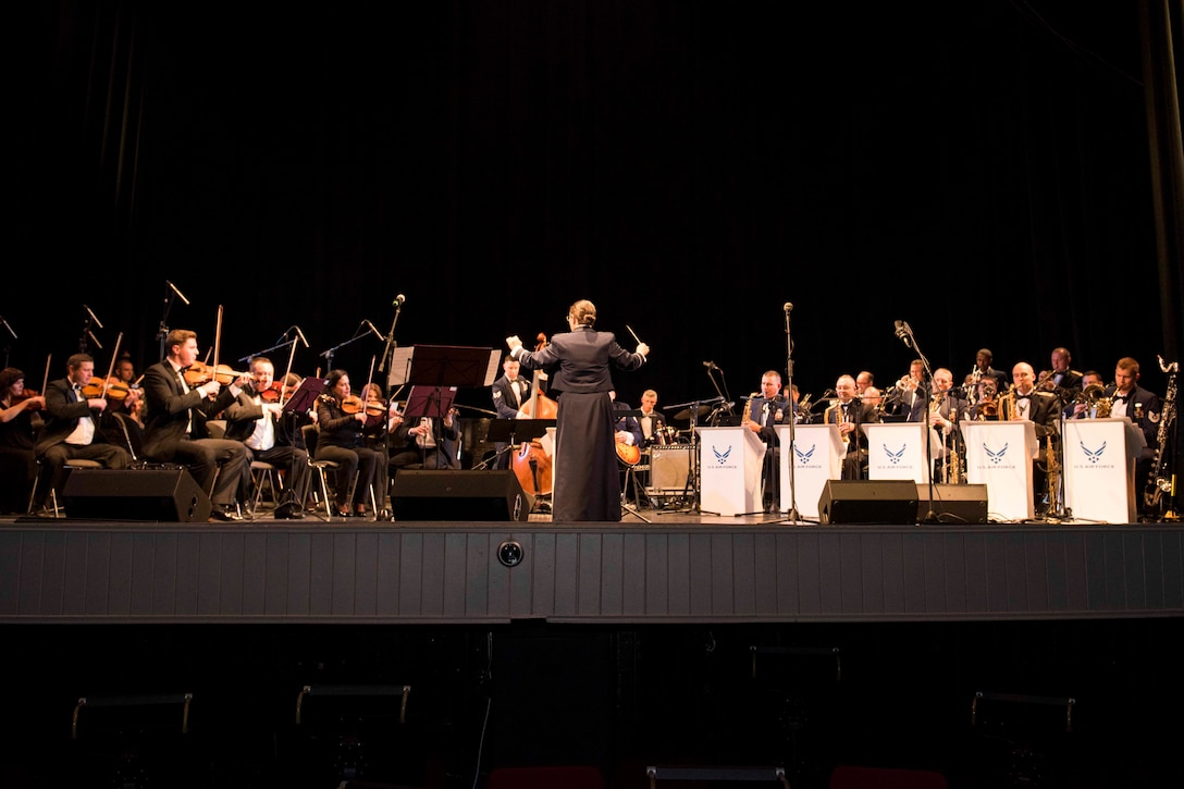 A conductor leads a large band with woodwind and brass instruments plays on stage.