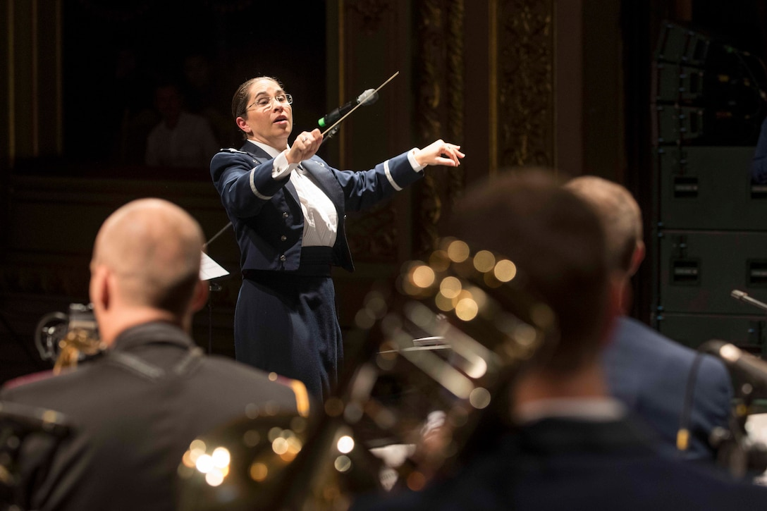 A female conductor waves her baton to musicians.