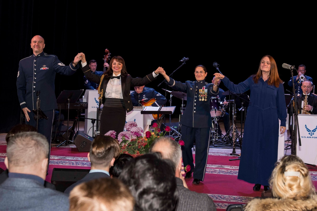 Four musicians, two of whom are dressed in Air Force dress blue uniform, hold hands on stage with a band behind them as they prepare to take a bow.