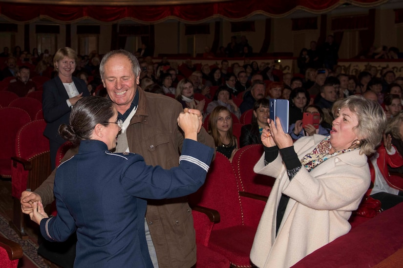 An Air Force band conductor dances with an audience member in the aisle of a theater as another theatergoer uses her phone to snap a photo.
