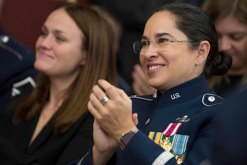 A female Air Force lieutenant colonel in dress blue uniform applauds in a crowd as someone smiles beside her.