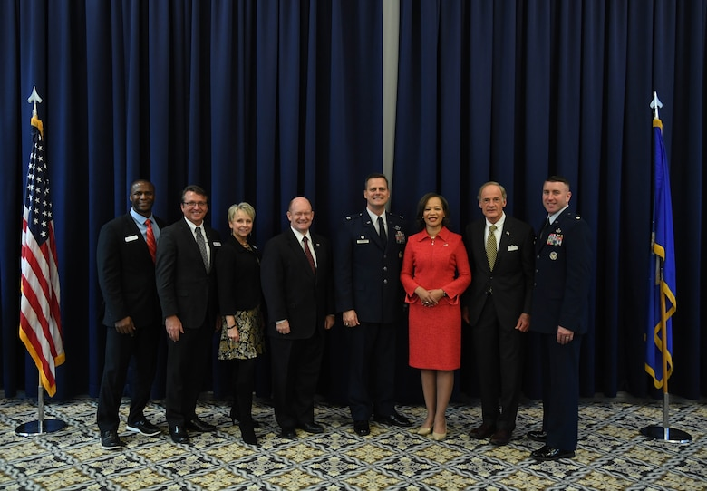 (From left) Evans Armantrading, Central Delaware Chamber of Commerce Military Affairs vice chairman; Shane Breakie, CDCC chairman; Judy Diogo, CDCC president; U.S. Senator Chris Coons; Col. Joel Safranek, 436th Airlift Wing commander; U.S. Rep. Lisa Blunt Rochester; U.S. Senator Tom Carper and Lt. Col. Robin Ryan, 512th Mission Support Group commander, pose for a photo following the State of the Base on Dover Air Force Base, Del., Nov. 25, 2019. (U.S. Air Force photo by Senior Airman Eric M. Fisher)