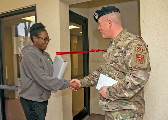 Airman 1st Class Amelia Franklin, dorm council president shakes hand with Chief Master Sgt. Anthony Fleming, 502nd Security Forces Group Command Chief at the entrance to the dorm's new Airman Learning Center at the dorms, November 22, 2019, Joint Base San Antonio-Randolph, Texas. The learning center features two Air Force network computers and a printer.