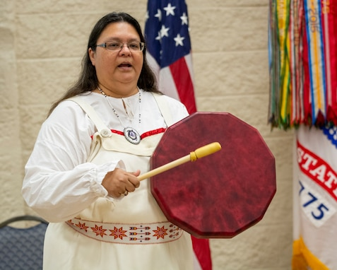 Guest speaker Kim Sigafus McIver sings and beats drum during observance