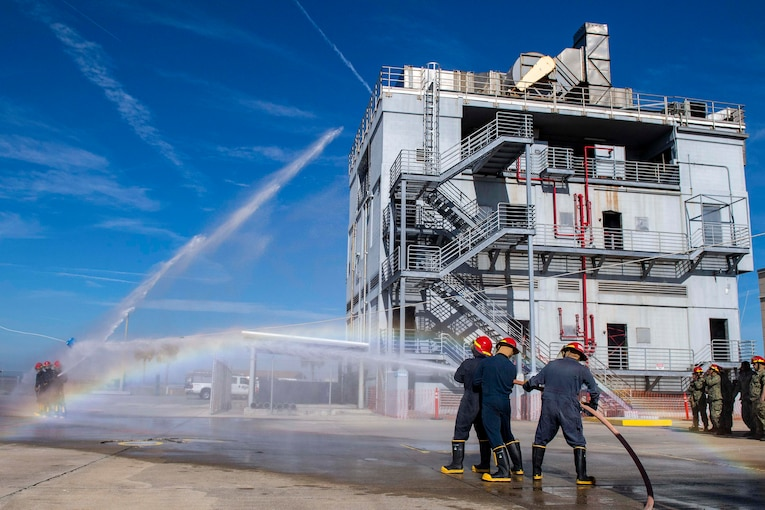 A group of sailors hold onto a water hose as it sprays a building.