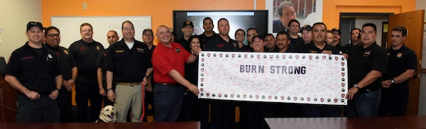 Brent Sabatino (in red shirt), U.S. Army Institute of Surgical Research Burn Center burn intensive care unit nurse, holds the banner for the Burn Strong program among first responders with the San Antonio Fire Department. The first responders attended a course instructed by Sabatino on advanced burn care that is part of the Burn Strong program, a partnership between the San Antonio Fire Department and USAISR in which paramedics and EMTs learn the basics of advanced burn and trauma life support care.
