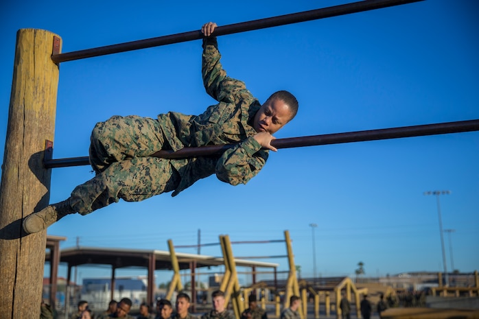 U.S. Marines and Sailors with Headuarters and Headquarters Squadron, Marine Corps Air Staion (MCAS) Yuma, participate in a squadron-wide obstacle course exercise on Nov. 8, 2019. The Marine Corps obstacle course is composed of various obstacles such as high and low logs, high bars, incline bars and traverse logs, and a rope climb. (Marine Corps photo by Lance Cpl. John Hall)