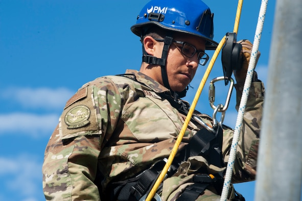 A photo of an Airman rappelling from a radio tower