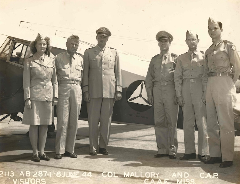 Lt. Col. J. Robert Dowd, Civil Air Patrol wing commander in Mississippi, was met by Col. L.C. Mallory, Columbus Army Air Field commanding officer, and a group of local CAP members when he landed at the Columbus Base to visit the city and address the Kiwanis Club at the Hotel Gilmer. (Left to right) Ida Billups (Ward), first female to make a solo flight with the Columbus Unit of CAP; Col. Mallory; Lt. Col. Dowd; Lt. Ralph Webb, CAP squadron commander in the district, and Sgts. Jack Parker and Billy Furr of the Columbus CAP squadron. (Photo courtesy of Civil Air Patrol)