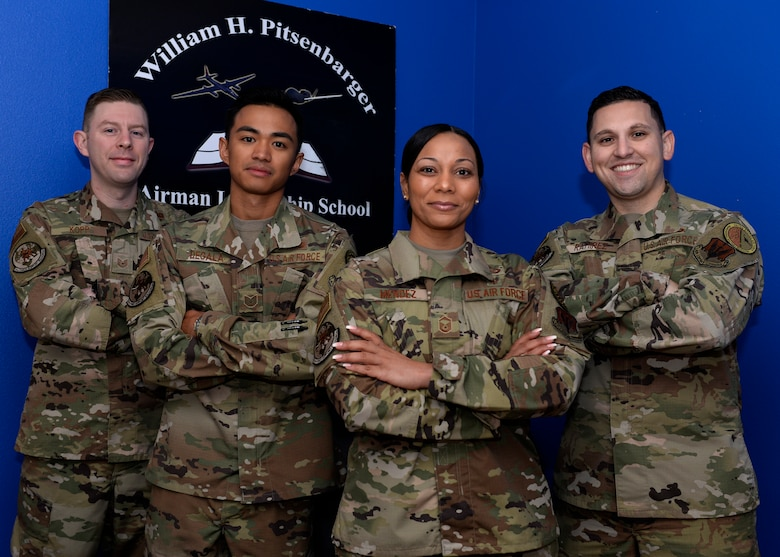 Four Airmen Leadership School instructors pose for a photo