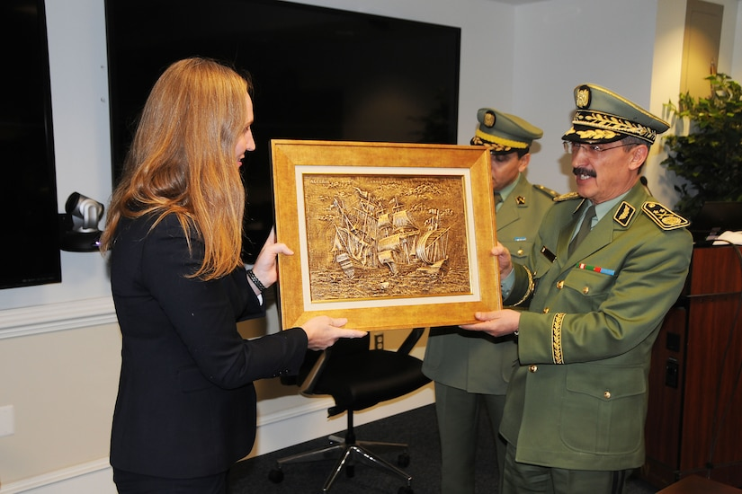 A military officer presents a framed metalwork scene to a civilian.