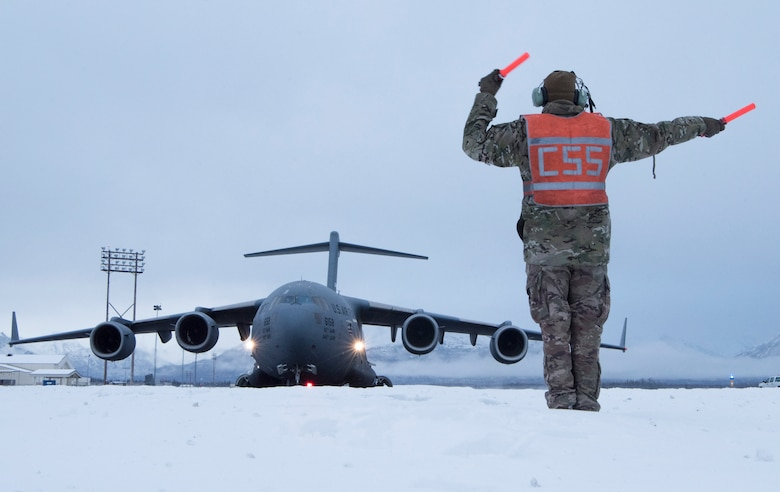 U.S. Air Force Staff Sgt. Joshua Sink, 921st Contingency Response Squadron, contingency response aircraft maintenance craftsman assigned to Travis Air Force Base, Calif., marshals a C-17 Globemaster III assigned to Travis AFB during cold weather aircraft maintenance procedures training at Joint Base Elmendorf-Richardson, Alaska, Nov. 19, 2019. The training prepared Airmen to operate in arctic environments.
