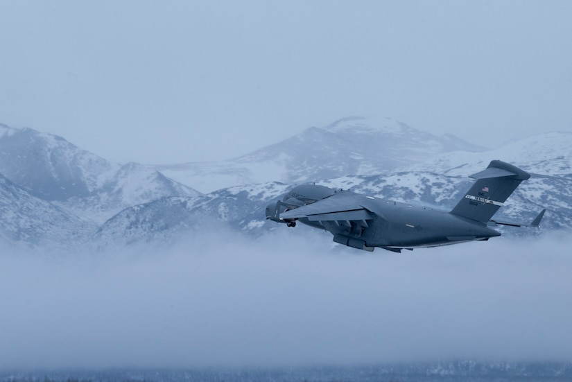 A U.S. Air Force C-17 Globemaster III assigned to Travis Air Force Base, Calif., flies over the Chugach Mountains during cold weather aircraft maintenance procedures training at Joint Base Elmendorf-Richardson, Alaska, Nov. 19, 2019. The training prepared Airmen to operate in arctic environments.