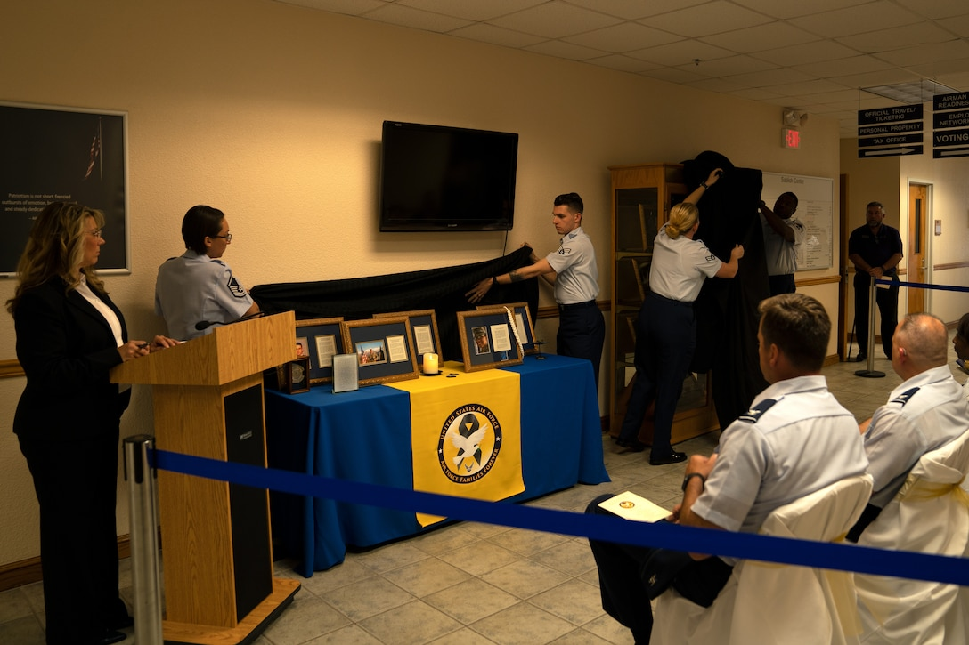 Airmen unveil the Fallen Heroes Cabinet display in the Sablich Center at Keesler Air Force Base, Mississippi, Sept. 30, 2019. The display was dedicated to Gold Star families to maintain the memory of fallen heroes and let the families know they are not forgotten. (U.S. Air Force photo by Airman 1st Class Kimberly Mueller)
