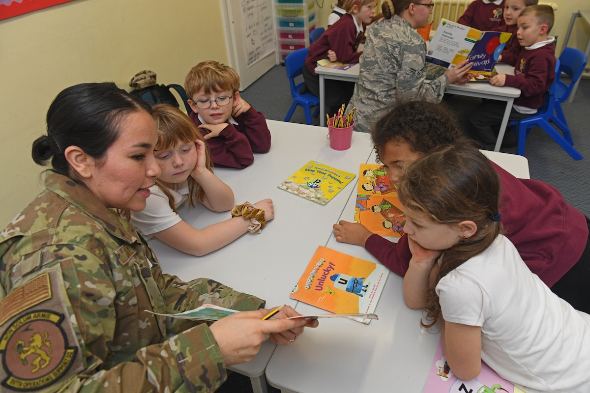 An airman reads to a group of children at a table.