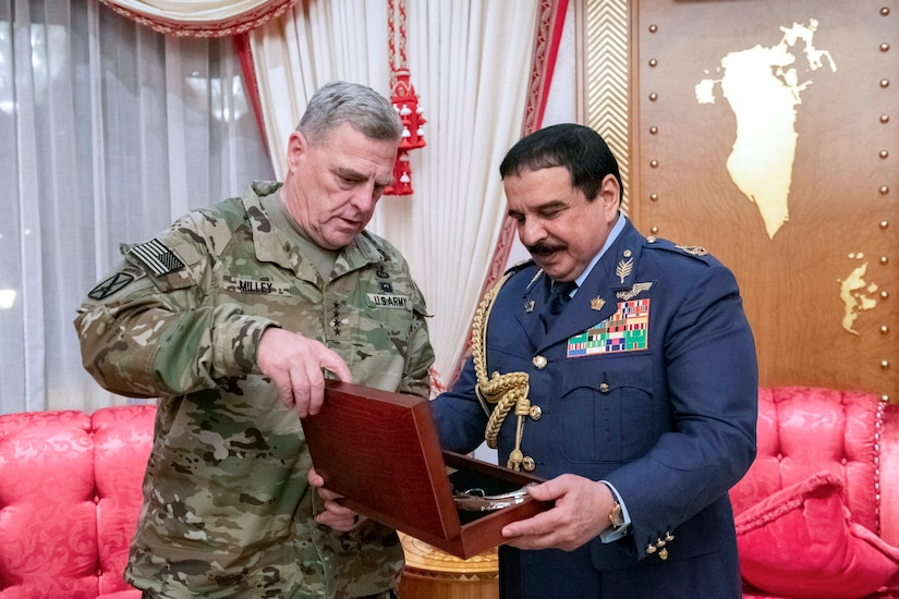 Two military leaders look into a small suitcase.