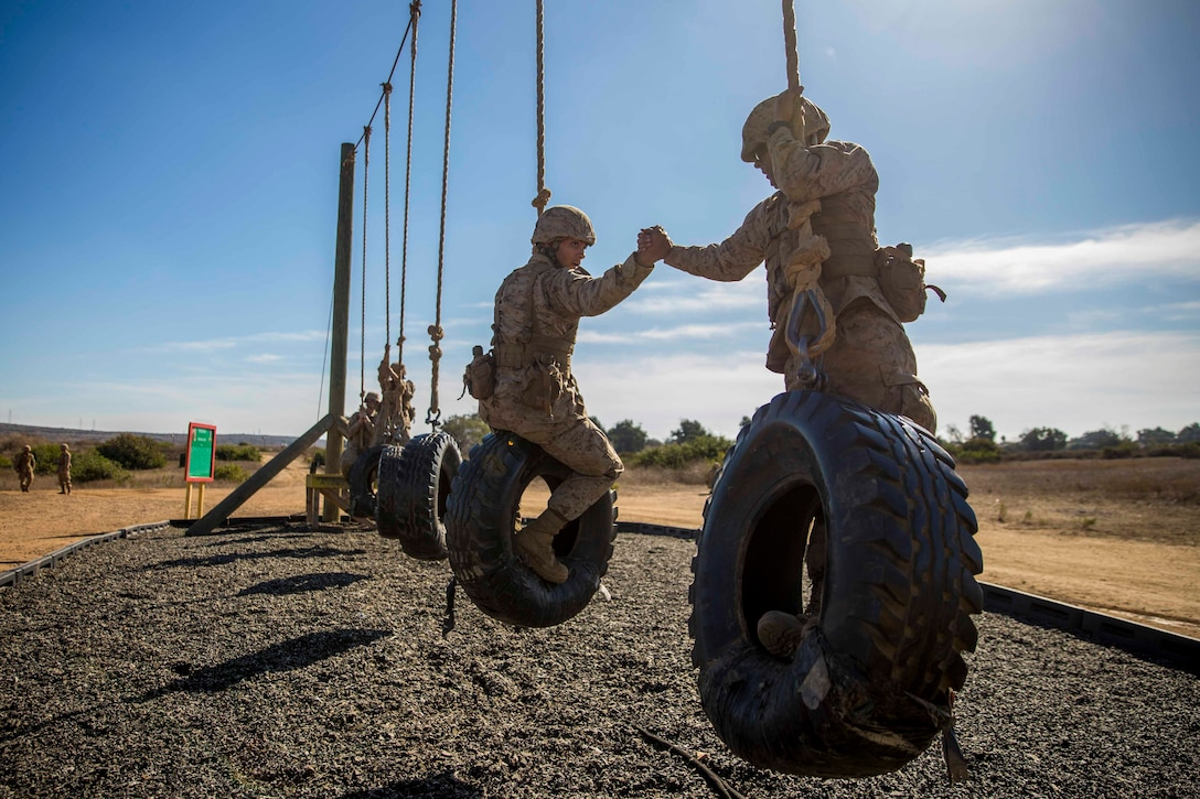 Two Marine Corps recruits hold hands as the clime a tire, rope obstacle.