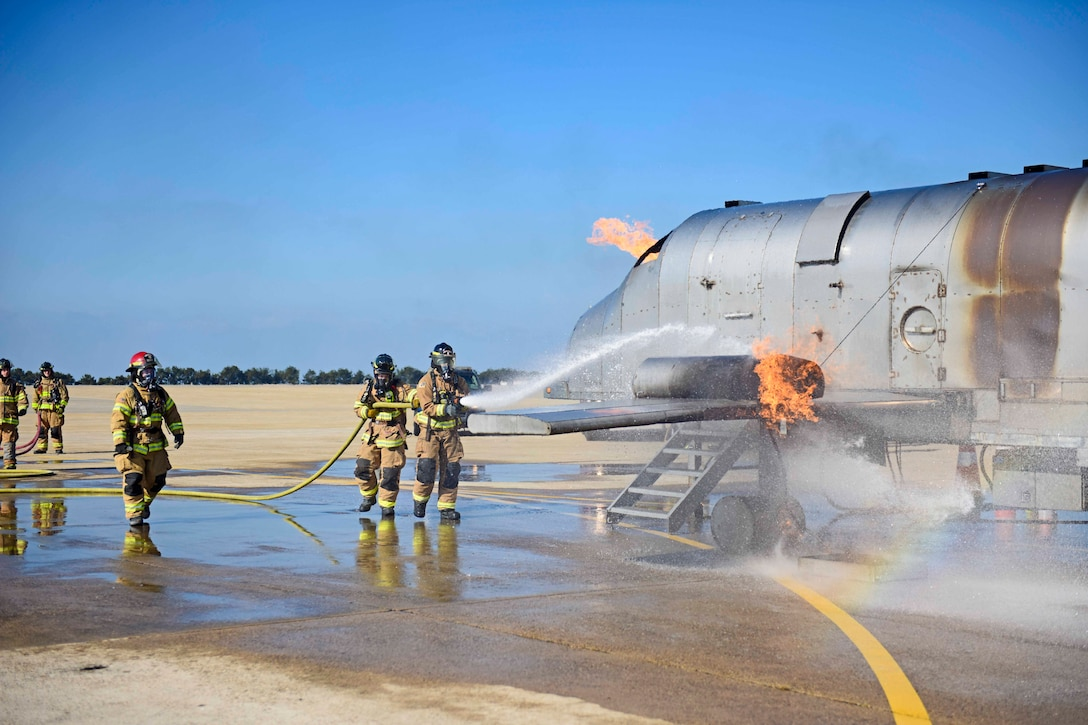 Airman use a water hose to spray an aircraft that is on fire.