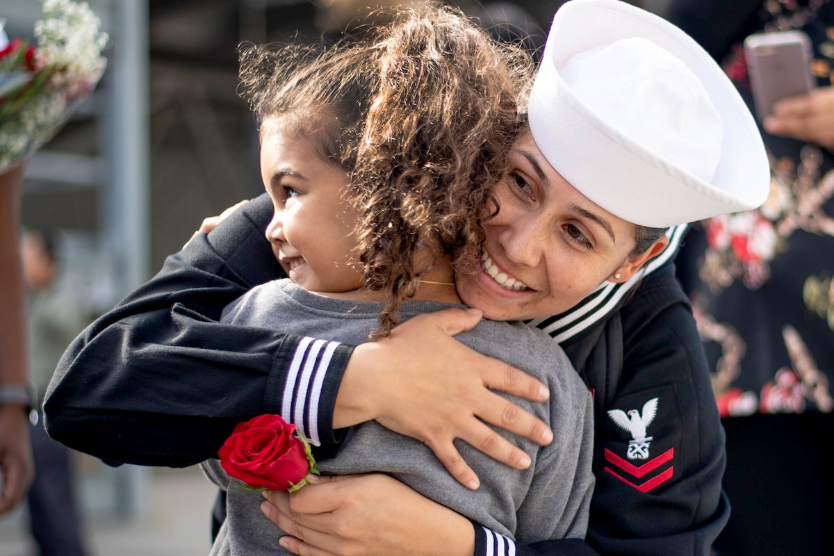 A female Navy officer embraces her child.