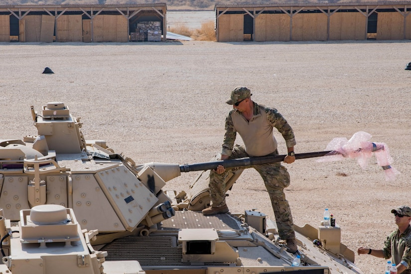 A soldier works on an armored vehicle.