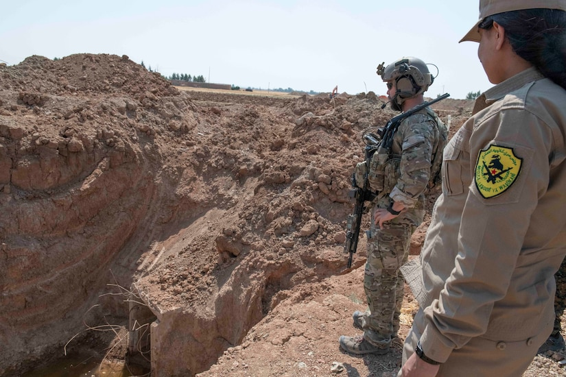 Two service members look down onto a construction site.
