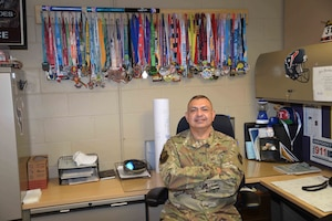 With his finisher medals in the background, Master Sgt. Raul Borrego, 433rd Aircraft Maintenance Squadron aircraft mechanic supervisor, is one of the Reserve Citizen Airmen that Chief Master Sgt. Pedro Saenz, 433rd Aircraft Maintenance superintendent, provides with support regarding his battle with Type 2 diabetes.