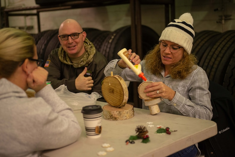 Airmen and families of the 354th Logistics Readiness Squadron build birch snowmen during a monthly squadron gathering, Nov. 7, 2019, at Eielson Air Force Base, Alaska. Attendees built both crafts and relationships while connecting with Air Force families. (U.S. Air Force photo by Capt. Kay NIssen)