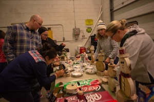 354th Logistics Readiness Squadron Airmen and Families select items to build a birch snowman at Eielson Air Force Base, Alaska, Nov. 7, 2019. Attendees gathered to build crafts and relationships during one of the squadron's monthly socials aimed at connecting Air Force families. (U.S. Air Force photo by Capt. Kay Nissen)