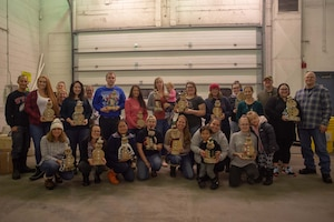 Airmen and families of the 354th Logistics Readiness Squadron pose for a photo during one of their monthly gatherings meant to build relationships, Nov. 7, 2019, at Eielson Air Force Base, Alaska. Participants built birch snowmen as part of a craft activity while they learned about each other. (U.S. Air Force photo by Capt. Kay Nissen)