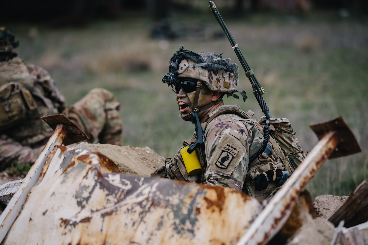 A soldier shouts while crouched behind an obstacle during training.