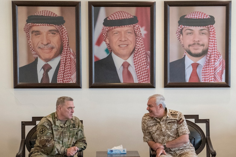 Two military leaders sit in chairs and talk to each other.