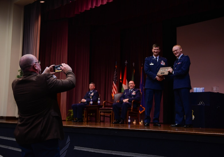 Col. Clinton ZumBrunnen, 437th Airlift Wing commander at Joint Base Charleston, South Carolina, takes a photo with a graduate from Specialized Undergraduate Pilot Training Class 20-03 while family members take photos Nov. 15, 2019, at Columbus Air Force Base, Miss. ZumBrunnen was the guest speaker for SUPT Class 20-03's graduation ceremony. (U.S. Air Force photo by Airman Davis Donaldson)
