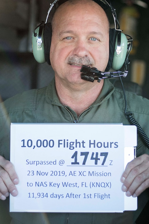 Chief Master Sgt. Terry Studstill, 700th Airlift Squadron flight engineer superintendent, poses with a sign showing the time and location where he attained 10,000 flight hours. He accomplished this major milestone Nov. 23, 2019 on a C-130H3 Hercules bound for Key West, Florida. (U.S. Air Force photo/Tech. Sgt. Andrew Park)