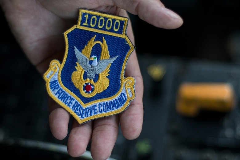 Chief Master Sgt. Terry Studstill, 700th Airlift Squadron flight engineer superintendent, shows a patch displaying 10,000 hours shortly before taking off on a flight from Dobbins Air Reserve Base, Ga. on Nov. 25, 2019. During the flight, he reached 10,000 hours, a major milestone in an aviator's career. (U.S. Air Force photo/Tech. Sgt. Andrew Park)