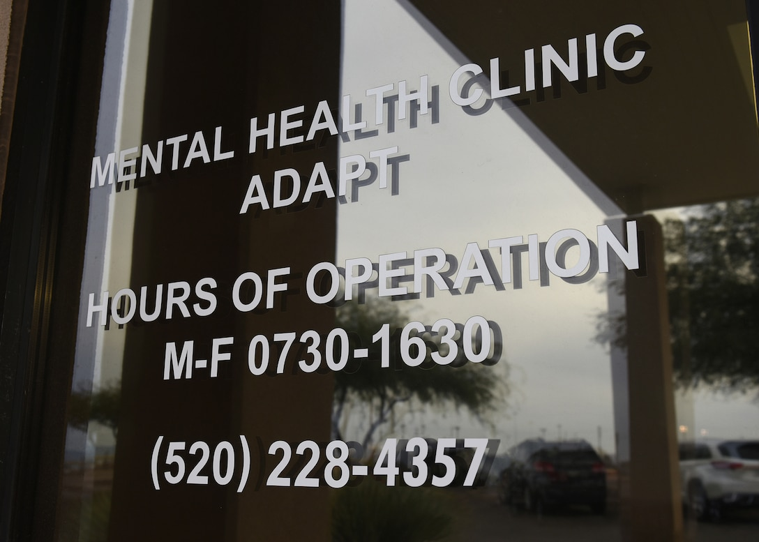 Hours of operation of a mental health clinic are displayed on building window