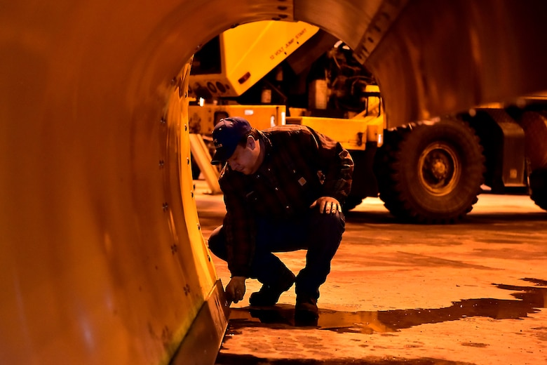 John Kowalski, the 354th Civil Engineer Squadron director of airfield snow removal operations, checks the blade on a plow on Eielson Air Force Base, Alaska, Nov. 21, 2019. Snow barn and vehicle maintenance Airmen work closely together to ensure all equipment is properly maintained due to extensive use and harsh winter conditions. (U.S. Air Force photo by Senior Airman Beaux Hebert)