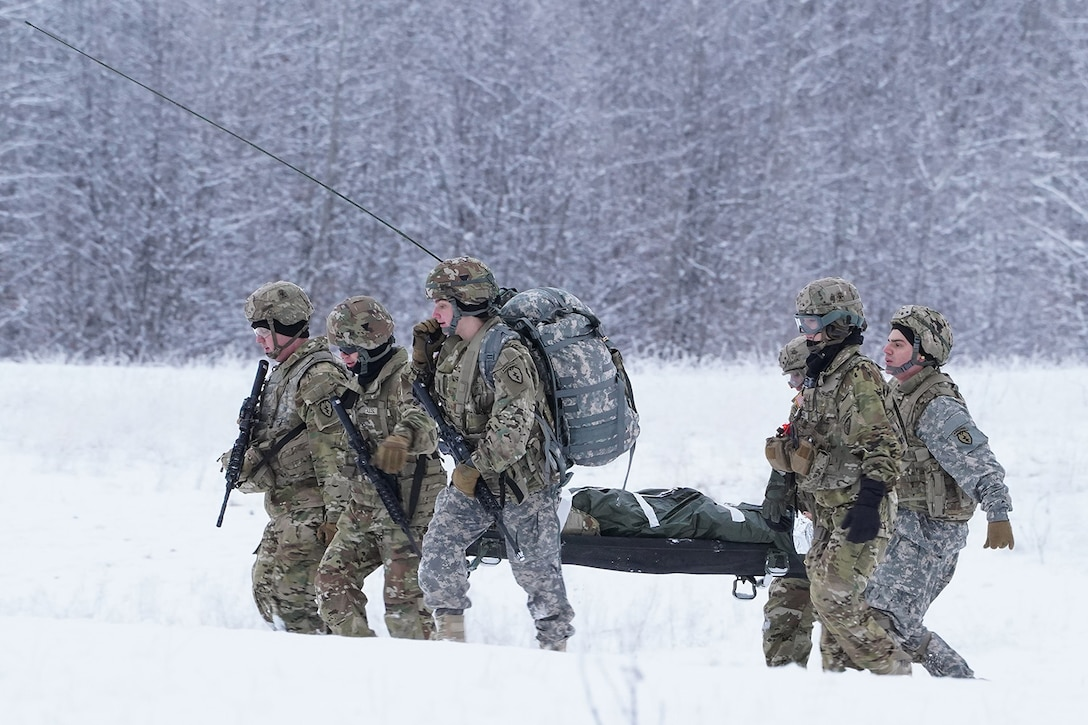Medics from the 6th Brigade Engineer Battalion (Airborne), 4th Infantry Brigade Combat Team (Airborne), 25th Infantry Division, U.S. Army Alaska, carry a simulated casualty to an extraction point while training with aviators from the Alaska Army National Guard at Neibhur Drop Zone, Nov. 26, 2019, to hone their life-saving and Medevac hoist skills for the paratroopers' upcoming rotation to the Joint Readiness Training Center at Fort Polk, La.